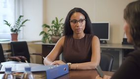 Mogen kvinna som förklarar hennes preferenser till afrikansk amerikanmedlet i fastighetföretag arkivfilmer