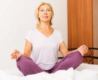 Mogen kvinna som gör yoga i säng fotografering för bildbyråer