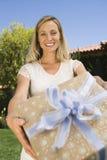 Mogen kvinna som ger gåvan Royaltyfria Foton