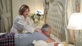 Mogen kvinna som ger massage till den höga mannen i säng stock video