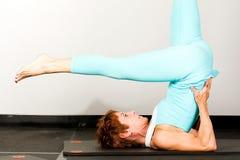 Mogen kvinna som gör Pilates Arkivbild