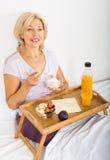 Mogen kvinna som har frukosten i säng Arkivfoton