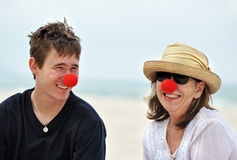 Mogen kvinna som har gyckel med den fullvuxna upp sonen på strandferie Royaltyfri Foto
