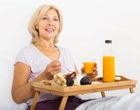 Mogen kvinna som har yoghurt med fruktsaft Arkivfoto