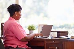 Mogen kvinna som hemma använder bärbara datorn på skrivbordet Royaltyfri Fotografi
