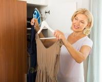 Mogen kvinna som hemma väljer klänningen Arkivbild