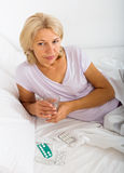 Mogen kvinna som lägger i säng med preventivpillerar och exponeringsglas Royaltyfri Bild