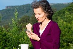 Mogen kvinna som ler med telefonen Arkivfoto