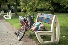 Mogen kvinna som ligger på bänk Arkivbild