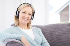 Mogen kvinna som lyssnar till musik på trådlös hörlurar fotografering för bildbyråer