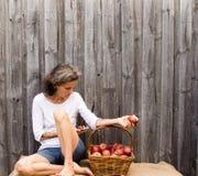 Mogen kvinna som placeras med telefonen och äpplen Arkivfoto