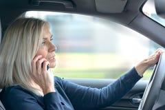 Mogen kvinna som pratar på hennes mobil i bilen royaltyfri bild