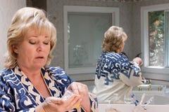 Mogen kvinna som räknar pills för att ta Fotografering för Bildbyråer