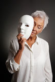Mogen kvinna som revaling den ledsna framsidan bak maskering Arkivfoto