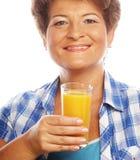 Mogen kvinna som rymmer ett exponeringsglas av orange fruktsaft Arkivfoto