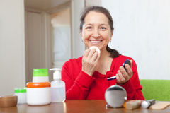 Mogen kvinna som sätter facepowder på framsida Arkivbilder