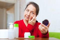 Mogen kvinna som söker efter ansiktsbehandlingskrynklor Arkivfoton