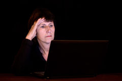 Mogen kvinna som sent arbetar på datoren på natten Royaltyfri Foto