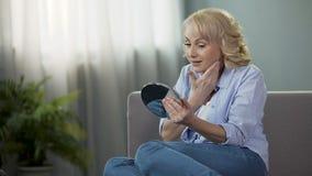 Mogen kvinna som ser in i en handspegel som tycker om reflexion Anti--ålder skönhetsmedel stock video