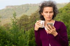 Mogen kvinna som ser telefonen i landskap Royaltyfri Fotografi