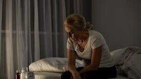 Mogen kvinna som sitter på säng som lider från fördjupning, piller på tabellen, problem royaltyfri fotografi