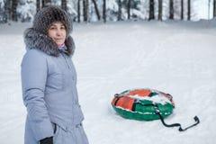 Mogen kvinna som står det near uppblåsbara snöröret i vinterskog Royaltyfri Bild