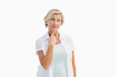 Mogen kvinna som tänker med handen på hakan Royaltyfri Foto