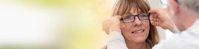 Mogen kvinna som testar nytt glasögon royaltyfri bild
