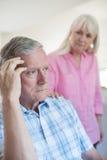 Mogen kvinna som tröstar mannen med den hemmastadda fördjupningen arkivfoto