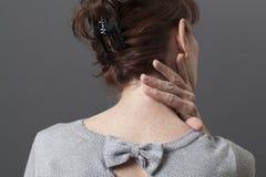 Mogen kvinna som trycker på hennes hals för lättnad Arkivfoton
