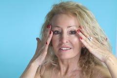 mogen kvinna som trycker på hennes hud royaltyfria bilder