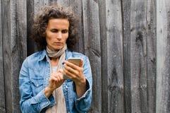 Mogen kvinna som utomhus använder den smarta telefonen Royaltyfri Bild