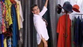 Mogen kvinna som visar ny kläder, når montering i kläderlager Lyckliga le kvinnapassager i modevisningslokal lager videofilmer