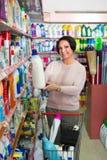 Mogen kvinna som väljer tvagningtvättmedel Arkivfoton