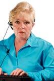 Mogen kvinnahörlurar med mikrofonoperatör Royaltyfri Foto