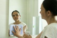 Mogen kvinnalokalvårdspegel och se hennes reflexion Arkivfoto
