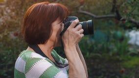 Mogen kvinnaskytte med fotokameran stock video