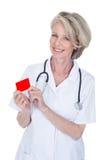 Mogen kvinnlig doktor Holding Visiting Card Fotografering för Bildbyråer
