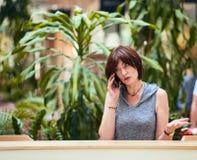 Mogen kvinnlig talande smartphone Arkivfoton