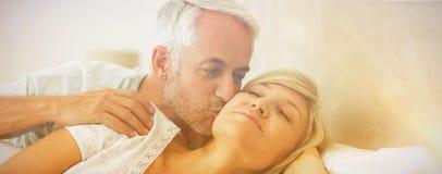 Mogen kyssande kvinnas för man kind i säng arkivbild