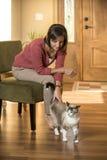 Mogen latinamerikansk kvinna med en katt Royaltyfri Bild
