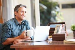 Mogen latinamerikansk man som hemma använder bärbara datorn på skrivbordet Arkivbilder