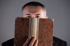 Mogen man bak en forntida bok Royaltyfri Foto