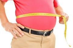 Mogen man för fett som mäter hans buk med mätningsbandet Royaltyfri Bild