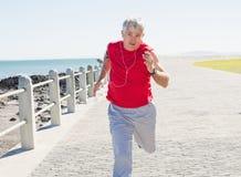 Mogen man för passform som joggar på pir Arkivfoto