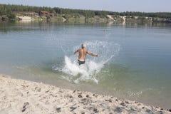 Mogen man i badningkortslutningar som kör in i det blåa sjöbadet Royaltyfria Bilder