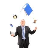 Mogen man i en dräkt som jonglerar med kontorstillförsel Arkivbilder