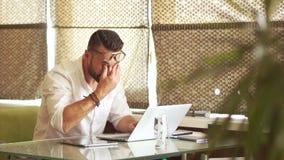 Mogen man i en vit skjorta och ett propert skägg som hårt arbetar i kontoret på datoren Avral på arbete, stopptid, slut av stock video