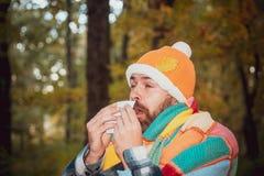 Mogen man i omslagslidande från förkylning Blåsa näsan med ett silkespapper som ser bedrövligt opassligt mycket sjukt sjukvård oc arkivfoton