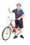 Mogen man med en cykel som ger upp en tumme Royaltyfria Bilder